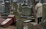 Illustrative: People walk through toppled graves at Chesed Shel Emeth Cemetery in University City, Mo., on Tuesday, Feb. 21, 2017. Authorities in Missouri are investigating after dozens of headstones were tipped over at the Jewish cemetery near St. Louis. (Robert Cohen /St. Louis Post-Dispatch via AP)