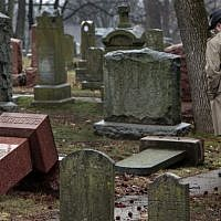 People walk through toppled graves at Chesed Shel Emeth Cemetery in University City, Missouri, on February 21, 2017. (Robert Cohen /St. Louis Post-Dispatch via AP)