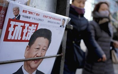 Women walk past a news stand displaying a Chinese news magazine fronting a photo of Chinese President Xi Jinping and US President Donald Trump, in Beijing, February 9, 2017. (AP/Andy Wong)