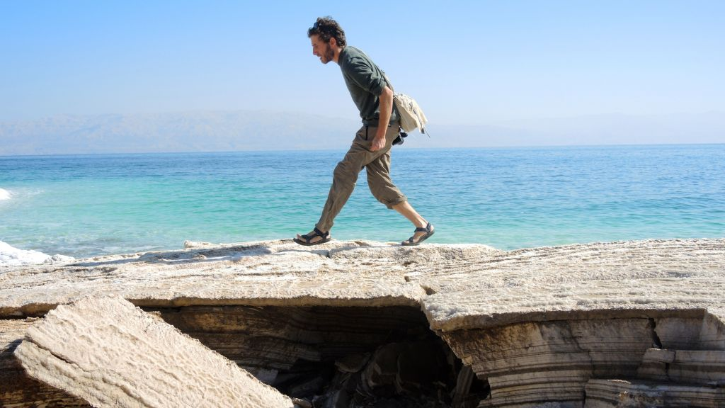 Geologist Ariel Meroz tiptoes over a thin crust covering a sinkhole on January 11, 2017. (Melanie Lidman/Times of Israel)