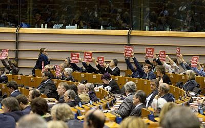 In this April 15, 2015, file photo, members of the European Parliament hold signs during a plenary session at the European Parliament in Brussels. (AP Photo/Virginia Mayo, File)