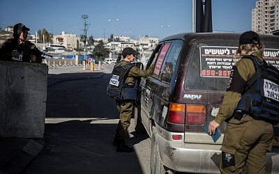 Illustrative photo of female Military Police officers checking the IDs and vehicles of Palestinians at the checkpoint at the Shuafat Refugee Camp in East Jerusalem, on December 22, 2015. (Hadas Parush/Flash90)