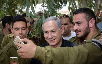 Benjamin Netanyahu taking a selfie with troops near the Gaza Border on May 3, 2016. (Amos Ben Gershom/GPO)