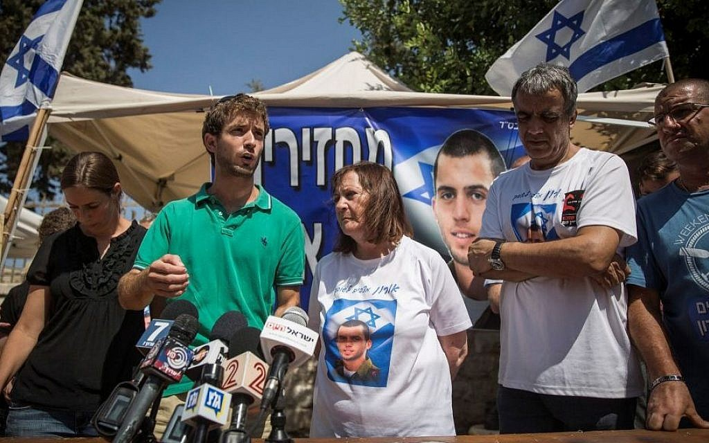 Parents of late Israeli soldiers Oron Shaul and Hadar Goldin speak with the press at the protest tent outside Prime Minister Benjamin Netanyahu's residence in Jerusalem on June 29, 2016. (Hadas Parush/Flash90)