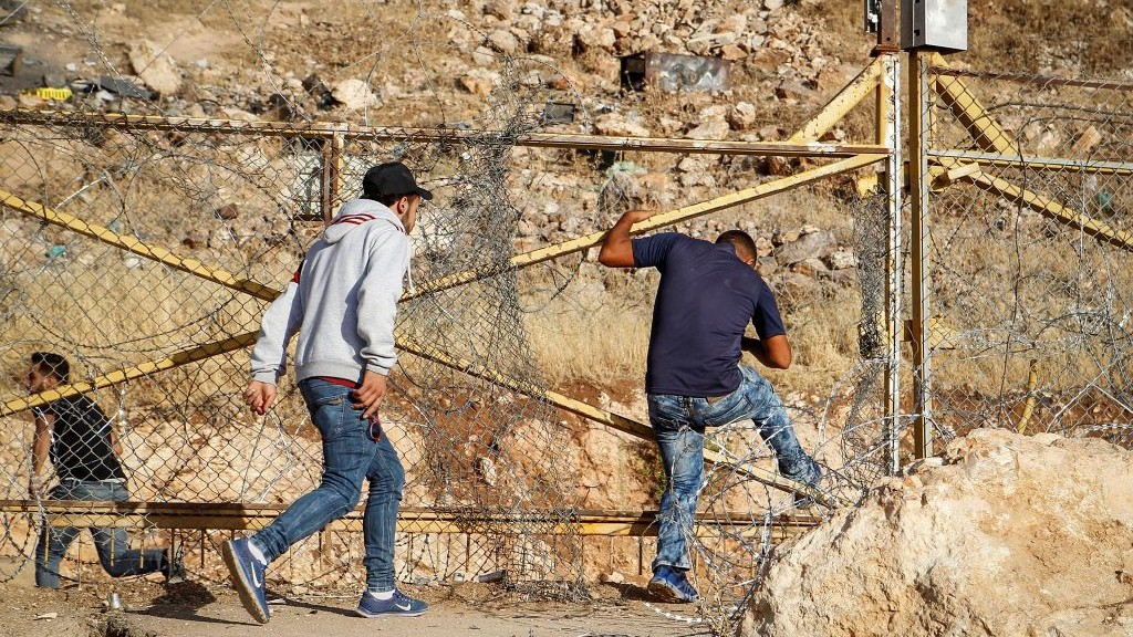 Palestinian men break through a gap in a fenced portion of the separation barrier between Israel and the West Bank on July 7, 2016. (Wisam Haslamoun/Flash90)