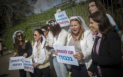 Activists, among them Zionist Union MK Ksenia Svetlova (second from right), holding signs and wearing wedding veils as they protest for the right to civil marriage in front of the Knesset in Jeruslaem on November 2, 2016. (Yonatan Sindel/Flash90)