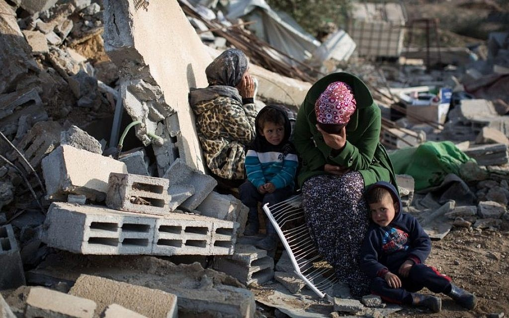 A Bedouin family sits in the ruins of their demolished home in the Bedouin village of Umm al-Hiran, southern Israel, January 18, 2017. (Hadas Parush/Flash90)