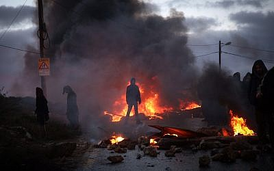 Protesters burn tires at the entrance to the illegal outpost of Amona, on February 1, 2017. Residents of the West Bank outpost of Amona have been given 48 hours to leave the hilltop community ahead of its court-ordered demolition. (Hadas Parush/Flash90)