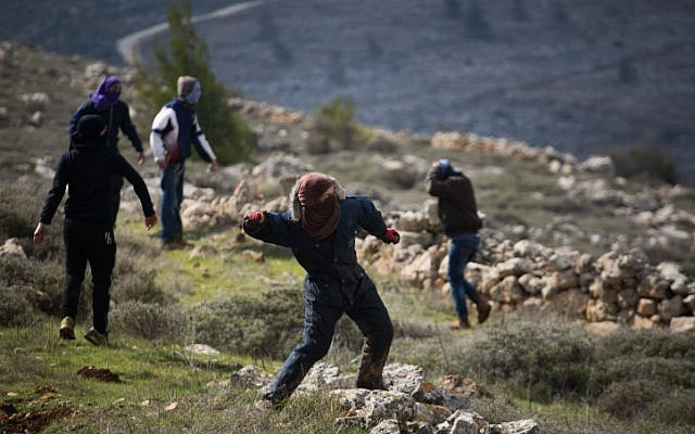 Young Jewish protesters throw rocks at police forces at the illegal outpost of Amona, on February 1, 2017, on the morning of the settlement's evacuation. (Hadas Parush/Flash90)