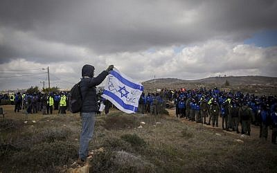 A man holds Israeli flag as Israeli security forces gather ahead of the evacuation of the illegal outpost of Amona, on February 1, 2017. (Miriam Alster/Flash90)