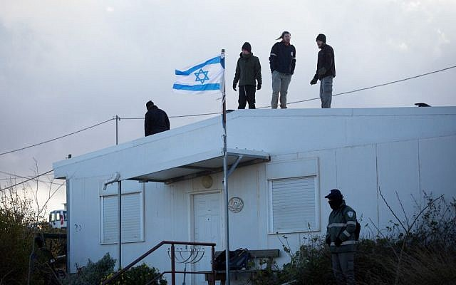 Israeli settlers stand on a rooftop during an evacuation operation at the illegal Israeli outpost of Amona on February 1, 2017. (Miriam Alster/FLASH90)