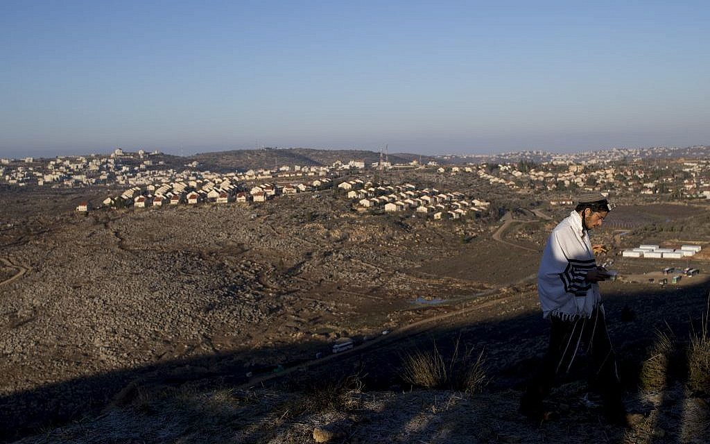 A man praying at the illegal outpost of Amona, with a view of West Bank settlements, on February 2, 2017. (Yonatan Sindel/Flash90)