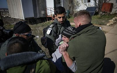 Illustrative. Israeli police forcibly evacuate a young man from the synagogue of the illegal outpost of Amona on February 2, 2017. (Yonatan Sindel/Flash90)