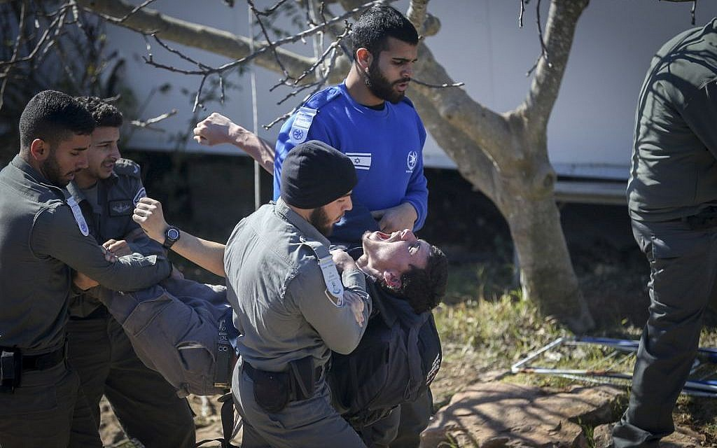 Police officers remove protesters as they evacuate the synagogue at the West Bank outpost of Amona on February 2, 2017 (Photo by Yonatan Sindel/Flash90)