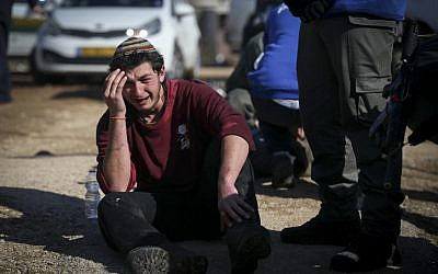 A protester weeps as police forces evacuate people from the synagogue at Amona, on the second day of the eviction of the illegal West Bank outpost on February 2, 2017. (Yonatan Sindel/Flash90)