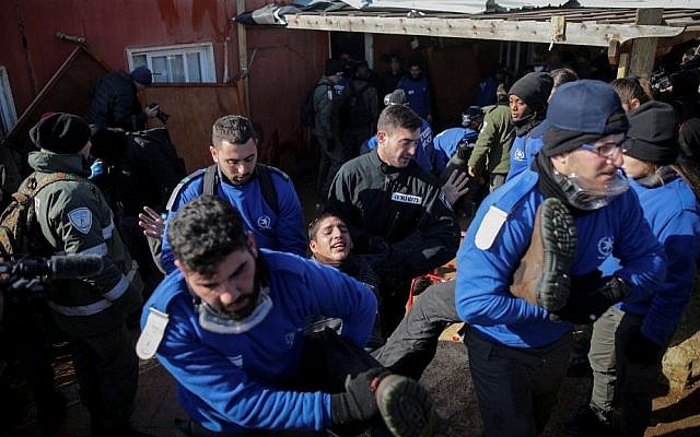 Israeli police forces evacuate people from the synagogue of the illegal outpost of Amona, on the second day of the eviction on February 2, 2017. (Yonatan Sindel/Flash90)