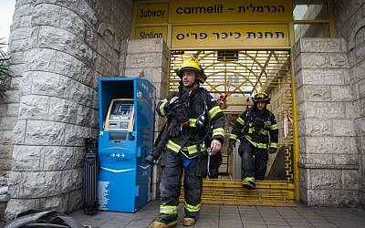 Firefighters attend the scene of a fire in the Carmelit underground train in Haifa on February 4, 2017. (Photo by Basel Awidat/FLASH90)