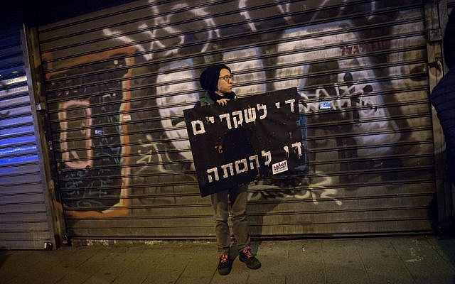 A protester holds a sign reading 'Enough lies, enough incitement' during a protest over the treatment of the Arab community, in Tel Aviv on February 4, 2017. (Photo by Miriam Alster/FLASH90)