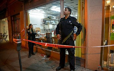 Police stand guard outside a sewing machine shop where a Palestinian man was captured after he opened fire at a bus outside the Petah Tikva central market on February 9, 2017. Five people were injured in the attack. (Flash90)