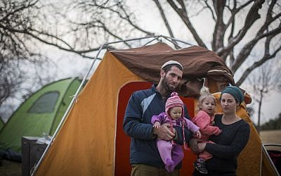 Tova and Neria Antman with their daughters pose for a photo by the tents set up as part of a protest of the Amona evacuation opposite the Israeli parliament on February 9, 2017. (Hadas Parush/Flash90)