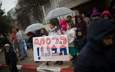 "Evicted residents from the Amona outpost protest in front of the Prime Minister's Office in Jerusalem holding a sign that reads ""You destroyed, (now) you (must) build"", on February 12, 2017. (Yonatan Sindel/Flash90)"