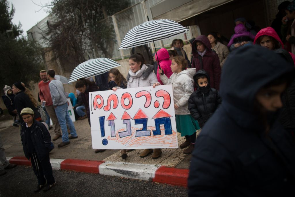 "Evicted residents from the Isreali settlement of Amona protest in front of the prime minister office in Jerusalem holding a sign that reads ""You've destroyed our home,"" on February 12, 2017. (Yonatan Sindel/Flash90)"