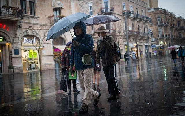 People walk in the rain on Jaffa street in downtown Jerusalem on February 14, 2017, as a rain storm hits the country. (Yonatan Sindel/Flash90)