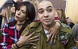 IDF Sgt. Elor Azaria, who shot dead a disarmed and injured Palestinian attacker in the West Bank city of Hebron in March 2016, is surrounded by family and friends as he awaits to hear his sentence in a courtroom at the Kirya military base in Tel Aviv, on February 21, 2017 (Jim Hollander/POOL)