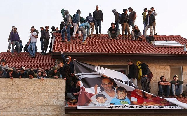 Protesters sit on a rooftop of a home during an operation to evacuate nine homes in the Jewish settlement of Ofra, in the West Bank, February 28, 2017. (Hadas Parush/Flash90)