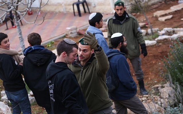 A Border Police officer argues with aight-wing activist during an operation to clear out nine houses in the Jewish settlement of Ofra, in the West Bank, on February 28, 2017. (Hadas Parush/Flash90)