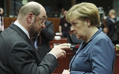 In this Dec. 19, 2013 photo then European Parliament President Martin Schulz, left, talks with German Chancellor Angela Merkel, during an EU summit at the European Council building in Brussels. (AP/Yves Logghe)