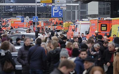 Travelers wait outside Hamburg Airport, northern Germany, after dozens of people were injured by an unknown toxic that likely spread through the airports' air conditioning system, February 12, 2017. (Axel Heimken/dpa via AP)