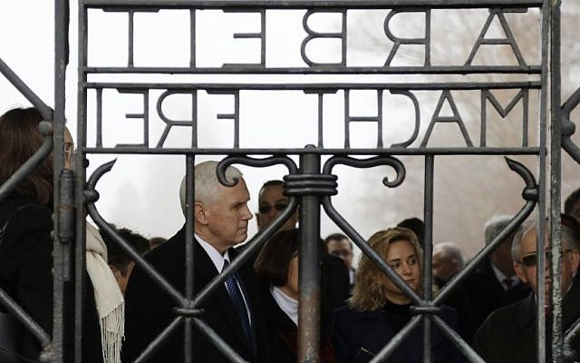 "US Vice President Mike Pence, second from left, stands behind the gate with the infamous writing ""Labor makes free"" during a visit to the former Nazi concentration camp in Dachau near Munich, southern Germany, Sunday, Feb. 19, 2017. (AP Photo/Matthias Schrader)"