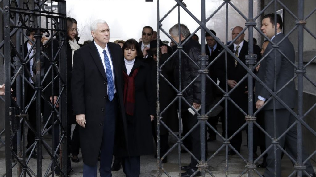 "US Vice President Mike Pence and his wife Karen go through the gate with the writing ""Works sets you free"" as they a visit the former Nazi concentration camp in Dachau near Munich, Germany, Sunday, Feb. 19, 2017. (AP Photo/Matthias Schrader)"