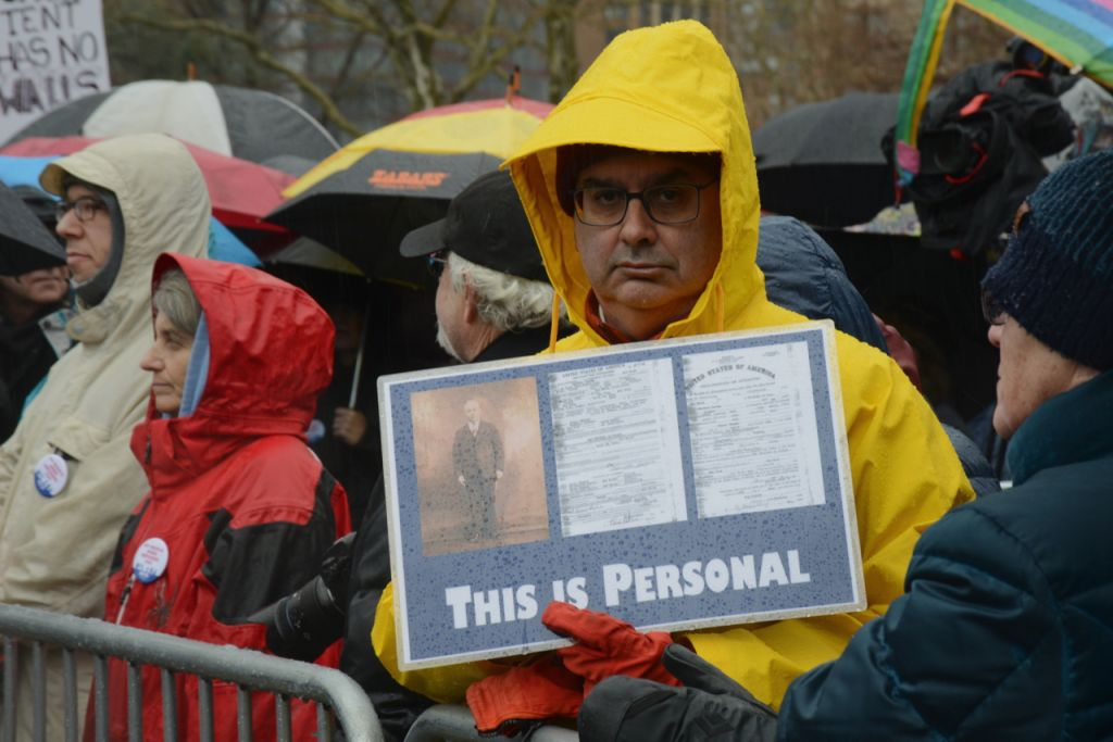 An attendee carries a sign, amid sleet and hail, during the Jewish Rally for Refugees in Battery Park, New York, on February 12, 2017. (Courtesy HIAS)