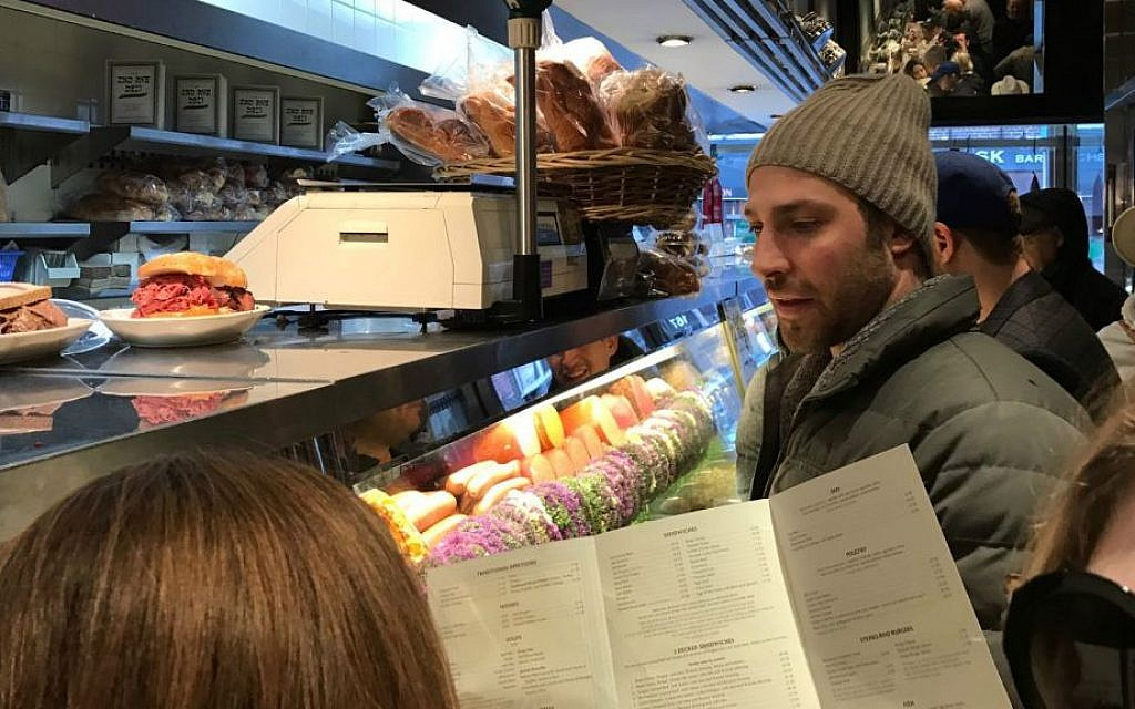 Shimmie Pesis gazes longingly into the deli case as he waits for a table at 2nd Avenue Deli in Midtown, New York. (Yaakov Schwartz/Times of Israel)