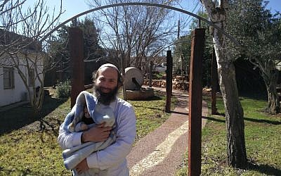 Former resident of the Amona outpost Avraham Rossana holding his 3-month-old baby in the Ofra Seminary campus, February 2, 2017. (Raoul Wootliff/Times of Israel)