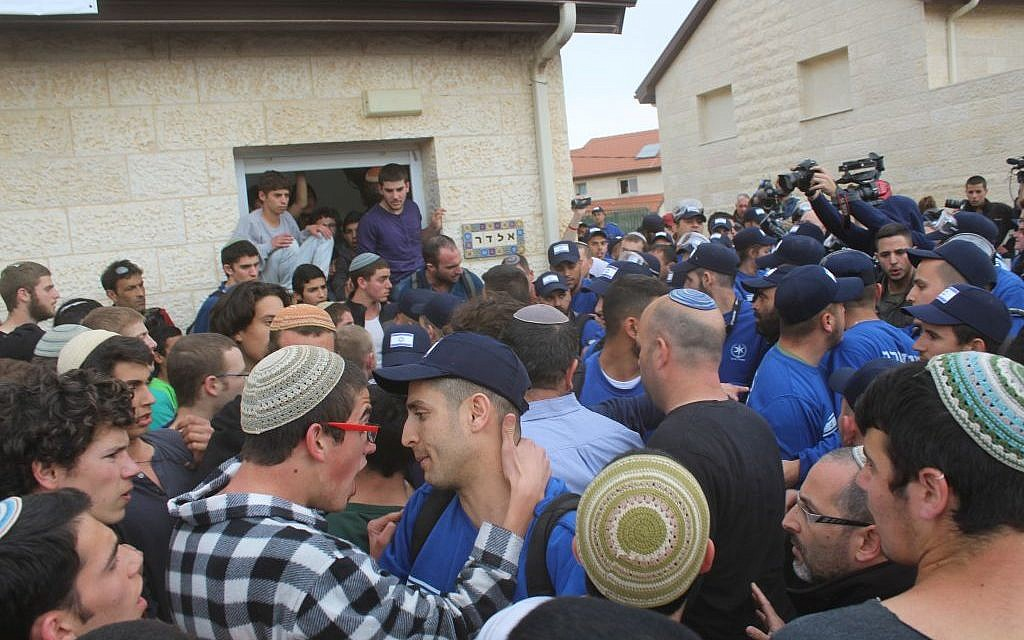 Protesters and police confront each other outside a home slated for demolition in the West Bank Settlement of Ofra on Tuesday February 28, 2017 (Raoul Wootliff/Times of Israel)