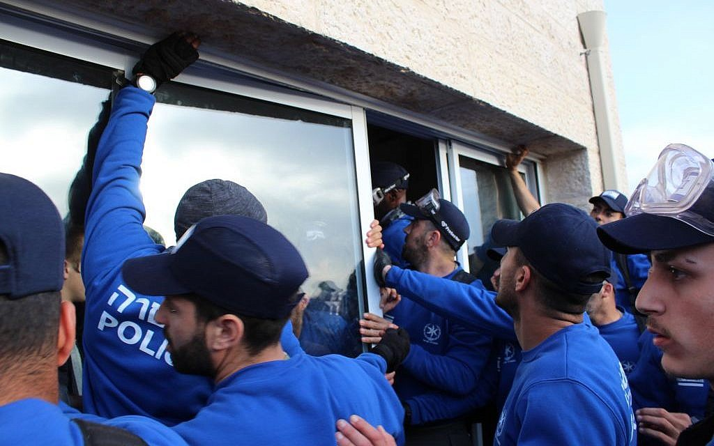 Police remove the windows of a house in Ofra as they prepare to clear the home of protesters on February 28, 2017 (Raoul Wootliff/ The Times of Israel)