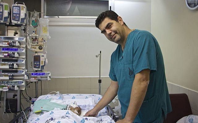 Dr Hagi Dekel, an Israeli cardiac surgeon at the Wolfson Medical Center in Holon, stands next to Yacub, a two-year-old Afghan whose life he saved, on February 23, 2017 (Dov Lieber / Times of Israel)