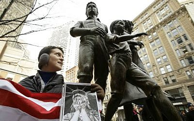 """Molly Hitt, of Boston, displays an American flag while standing in front of a memorial to the Irish potato famine, right, during a rally called """"We Will Persist,"""" Tuesday, Feb. 21, 2017, in Boston. (AP Photo/Steven Senne)"""