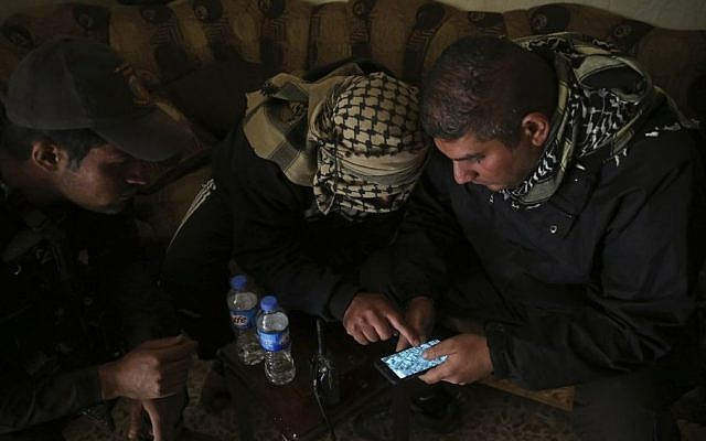 In this Nov. 25, 2016 photo, special forces Lt. Col. Ali Hussein, right, listens to an Iraqi informant, center, giving information about Islamic State militant positions on a mobile map, in the Bakr front line neighborhood, in Mosul, Iraq. (AP Photo/Hussein Malla)