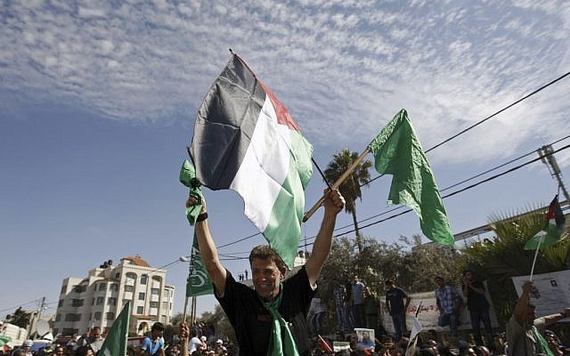 Hamas terrorist Nael Barghouti waves a green Islamic flag and a Palestinian flag to the crowd after arriving in the West Bank city of Ramallah after he was released as part of an exchange for Gilad Shalit, an Israeli soldier held by Hamas, October 18, 2011. (AP/Majdi Mohammed)