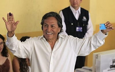 In this April 10, 2011 file photo, then presidential candidate Alejandro Toledo holds up his ink-stained finger and identification card after voting in the general elections, in Lima, Peru. (AP Photo/Martin Mejia, File)