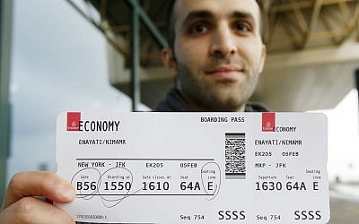 Iranian-born bio-engineer researcher Nima Enayati holds up his boarding pass at the Milan's Malpensa International airport in Busto Arsizio, Italy, Sunday, Feb. 5, 2017. (AP Photo/Antonio Calanni)