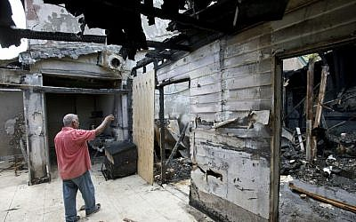 In a Thursday, Sept. 15, 2016, file photo, Farhad Khan, who has attended the Islamic Center of Fort Pierce for more than seven years, shows members of the media its charred remains, in Fort Pierce, Fla. (AP Photo/Wilfredo Lee, File)
