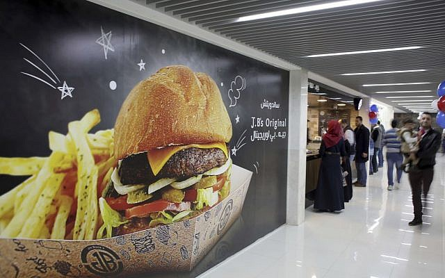 Palestinians buy fast food from the food court in a new indoor shopping mall in the Gaza Strip, in Gaza City, Feb. 18, 2017.  (AP Photo/ Khalil Hamra)
