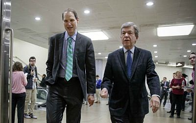Sen. Ron Wyden, D-Oregon, left, and Sen. Roy Blunt, R-Missouri, walk to a closed intelligence briefing with FBI Director James Comey, Friday, Feb. 17, 2017, on Capitol Hill in Washington. (AP Photo/J. Scott Applewhite)