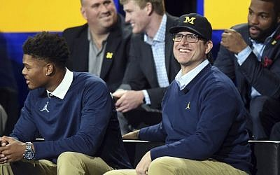 "Michigan head football coach Jim Harbaugh smiles as he sits on stage during the ""Signing of the Stars"" event on national signing day at Crisler Center in Ann Arbor, Michigan, Wednesday, Feb. 1, 2017. (Melanie Maxwell/The Ann Arbor News via AP)"