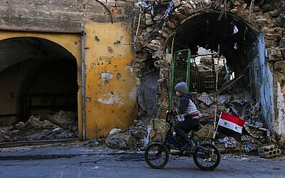 In this January 20, 2017 file photo, a Syrian boy rides his bike past the destruction in the once rebel-held Jalloum neighborhood of eastern Aleppo, Syria. (AP Photo/Hassan Ammar, File)